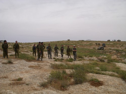 Soldiers standing with the illegal outpost in the background