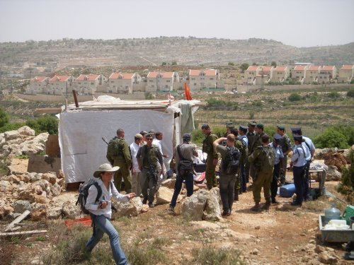 Soldiers and police around the settler's structure