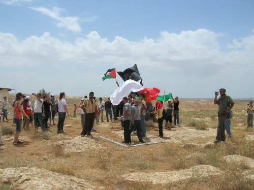Palestinians waving their flag and colors after their 'sukkah' was dismantled